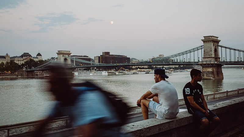 10 Day-and-night-men-travel-budapest-men-hanging-out-in-front-of-chain-bridge
